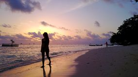 P02068 Aerial flying drone view of Maldives white sandy beach sunrise sunset happy 1 person young beautiful young woman. Aerial flying drone view of Maldives royalty free stock images