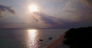 Aerial flying drone view of Maldives white sandy beach sunset sunrise on sunny tropical paradise island with aqua stock video footage