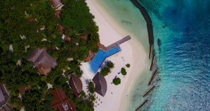 Aerial flying drone view of Maldives white sandy beach swimming pool in luxury 5 star resort hotel relaxing. Holiday vacation on sunny tropical paradise island stock video