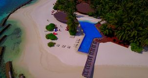 Aerial flying drone view of Maldives white sandy beach swimming pool in luxury 5 star resort hotel relaxing stock video footage