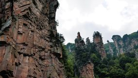 Aerial Flying Near The Rock Pillars In The Zhangjiajie Mountains. Aerial flying near vertical high cliff pillars and columns in the mountains of Zhangjiajie Park stock footage