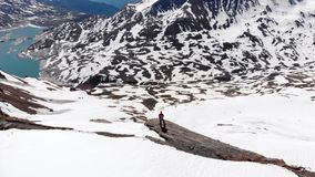 Aerial: flying over hiker on snowy mountain top, ski touring mountaineering snow mountain, panoramic view on the alps, conquering. Adversity, achieving success stock video footage