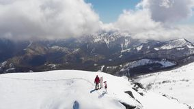 Aerial: flying over hiker on snowy mountain top, ski touring mountaineering snow mountain, panoramic view on the alps, conquering. Adversity, achieving success stock footage