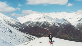 Aerial: flying over hiker on snowy mountain top, ski touring mountaineering snow mountain, panoramic view on the alps, conquering. Adversity, achieving success stock video