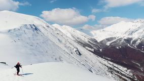Aerial: flying over hiker walking towards snowy mountain top, ski touring mountaineering snow mountain, panoramic view on the alps. Conquering adversity stock footage