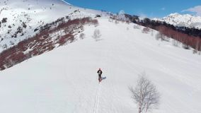 Aerial: flying over hiker walking towards snowy mountain top, ski touring mountaineering snow mountain, panoramic view on the alps. Conquering adversity stock video footage
