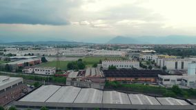 Aerial: flying over industrial district and farmland with mountain view and clouscape in the background, Turin, Italy.  stock video footage