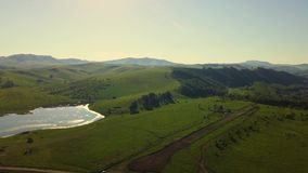 Aerial: Flying over sunny fields and mountains, during sunset. Also visible: forest, pasture, arable land lake stock video footage