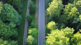 Aerial flying tilted down over modern and straight highway showing dark grey asphalt roads for traffic car moving both. Ways forest and grassland landscape 4k stock footage