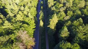 Aerial flying tilted down over modern and straight highway showing dark grey asphalt roads for traffic car moving both. Ways forest and grassland landscape 4k stock video footage