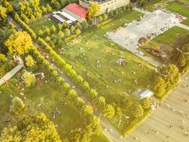 Aerial flying view from above of people having fun on the grass in city park on summer day royalty free stock image