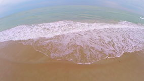 Aerial flyout from ocean tide stock video footage