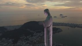 Aerial flight over Cristo Redentor Christ Redeemer Rio de Janeiro statue in incredible brasilian evening sunset seascape