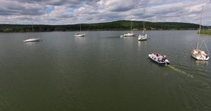 Aerial follows the boat at low altitude. Drone flying over motor boat with people stock footage