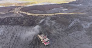 Aerial footage of big red truck in a career of mining. Delivery by the motor transport from a pit. Aerial footage stock footage