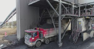 Aerial footage of big red truck in a career of mining. Delivery by the motor transport from a pit. Aerial footage stock video footage