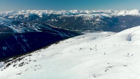 Aerial footage of Blackcomb mountain and skiers on a sunny day. stock footage