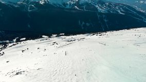 Aerial footage of Blackcomb mountain and skiers on a sunny day. stock video footage