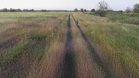 Aerial footage of boy riding bike. Countryside road. Agricultural field in summer. Ukrainian nature