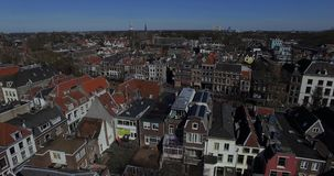 Aerial footage of the city roofs and canal in Netherlands. Drone flying above houses in Holland