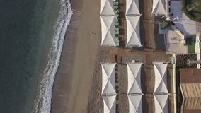 Aerial footage of coast line with umbrellas on sandy beach. Bird eye view stock footage