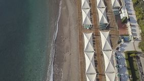 Aerial footage of coast line with umbrellas on sandy beach. Bird eye view stock video
