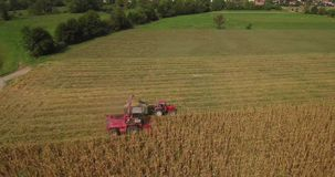 Aerial footage of corn harvest with combine and tractor on a field on a field stock footage