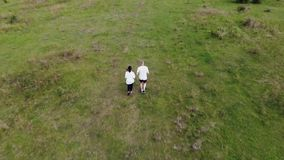 Aerial footage from couple running on the Hungarian meadow stock footage