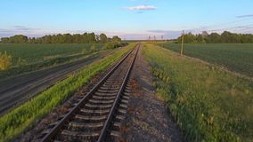 Aerial footage from a drone flying along a train track in a rural stock video footage