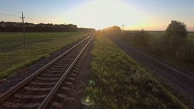Aerial footage from a drone flying along a train track in a rural. Area landscape at dusk stock video