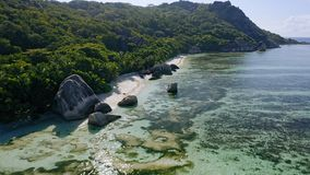 Aerial footage fly along famous Anse Source d`Argent tropical beach with unique granite boulders. Sunshine reflect on