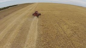 Aerial footage following harvester at work in crop stock video footage