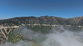 Aerial footage of forest-covered hills, blue skies and clouds on the slopes near Big Bear Lake, California, USA