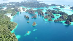Aerial Footage of Gorgeous Limestone Islands in Raja Ampat. Limestone islands rise from a gorgeous, tropical lagoon in Wayag, Raja Ampat, Indonesia. This unique stock footage