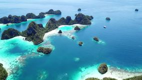 Aerial Footage of Gorgeous Rock Islands in Raja Ampat. Limestone islands rise from a gorgeous, tropical lagoon in Wayag, Raja Ampat, Indonesia. This unique stock video