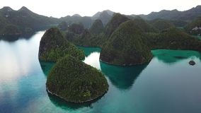 Aerial Footage of Islands and Lagoon in Raja Ampat. Rugged limestone islands, surrounded by coral reefs, are found in an idyllic, tropical lagoon in Wayag, Raja stock video