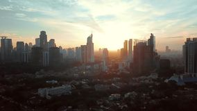 Aerial footage of Jakarta city at sunset. Beautiful aerial footage of Jakarta city at sunset time with silhouette of skyscrapers from a drone flying down. Shot stock video footage