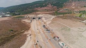 Aerial footage of large highway construction project with tunnels and bridges. Aerial footage of a large scale highway construction project stock video footage