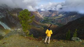 Aerial footage of a man standing near a tent in front of mountain valley. Small camping. guy stands looking at the great view stock footage
