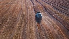 Aerial footage of a modern tractor plowing dry field, preparing land for sowing. seeding at the end of the season. Plant stock video footage