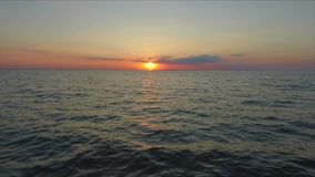 Aerial footage Ocean fly over at sunset, just above the ocean waves facing the sun stock video