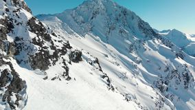 Aerial footage of the peak of Blackcomb mountain on a sunny day. stock video footage