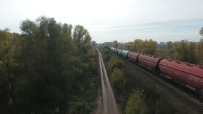 Aerial footage of railway and freight train. Flying over railway and freight train moving fast. Drone moving backwards. 4K Aerial stock footage clip stock video footage