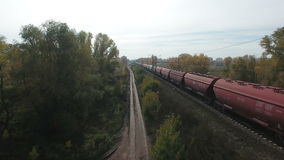 Aerial footage of railway and freight train. Flying over railway and freight train moving fast. Drone moving forward. 4K Aerial stock footage clip stock video
