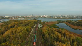 Aerial footage of railway and freight train. Flying over railway and freight train moving fast to the city. Drone moving forward at at high altitude. 4K Aerial stock footage