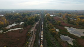 Aerial footage of railway and freight train. Flying over railway and freight train moving fast to horizon. Drone moving forward at at high altitude. 4K Aerial stock video footage