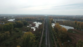 Aerial footage of railway  stretches among lakes. Flying over railway that stretches among lakes. Drone moving backrwards at at high altitude. 4K Aerial stock stock video footage