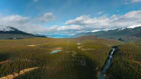 Aerial footage of a road through a dense coniferous forest with a lake and a river in Alberta, Canada