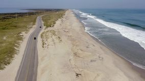 Aerial view of road between ocean side and sound side. 4k. Aerial footage of road with many cars and ocean flying with drone between cities stock video footage