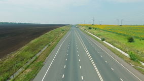 Aerial footage of road and transport, people traveling by cars on a freeway. Amongst sunflower field stock footage